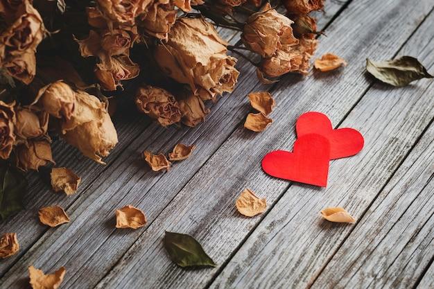 Dois corações vermelhos com buquê de rosas secas em fundo de madeira