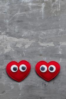 Dois corações vermelhos com olhos em fundo de cerâmica