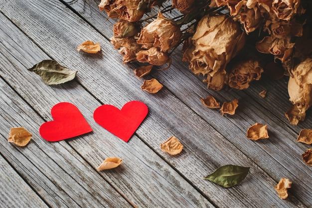 Dois corações vermelhos com pétalas de rosas secas na mesa de madeira