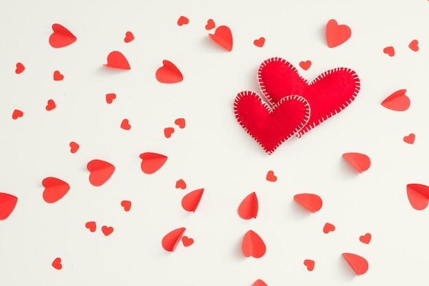 Dois corações vermelhos de feltro feitos à mão em branco de padrão de amor.