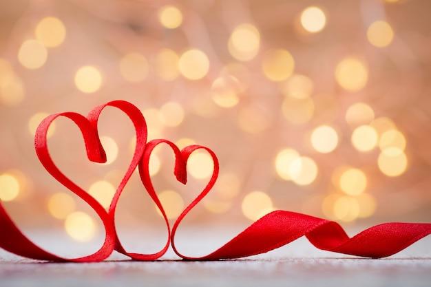 Dois corações vermelhos de fita. cartão de dia dos namorados.
