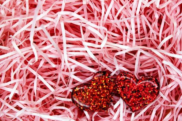 Dois corações vermelhos de plástico em um fundo rosa feito de tiras de papel