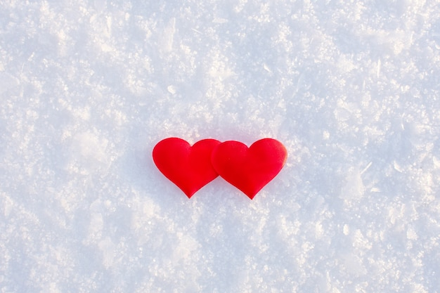 Dois corações vermelhos deitado na neve limpa branca em um dia ensolarado de inverno.