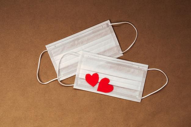 Dois corações vermelhos e máscara médica de proteção facial branca