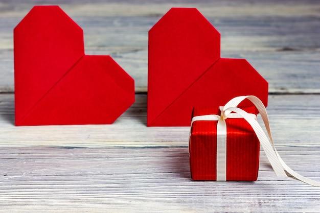 Dois corações vermelhos e um pequeno presente vermelho sobre uma mesa de madeira clara.
