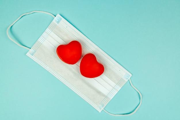 Dois corações vermelhos em máscara de proteção médica em superfície azul clara