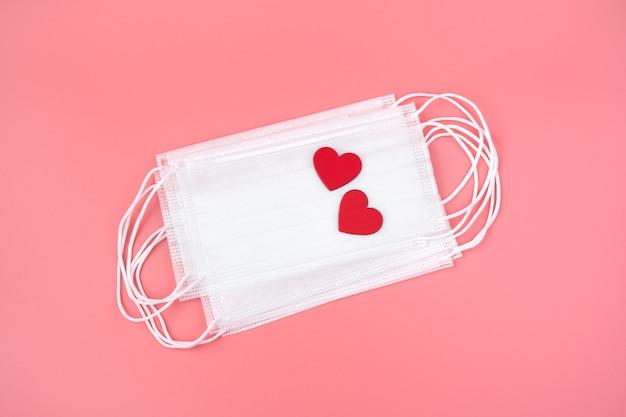 Dois corações vermelhos em máscaras médicas brancas. vista de cima, com espaço para copiar. conceito 14 de fevereiro.
