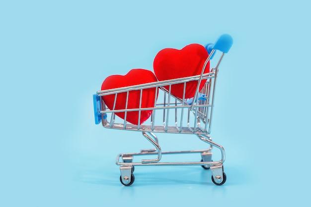 Dois corações vermelhos em um carrinho de compras em uma mesa azul.
