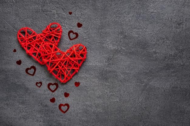 Dois corações vermelhos em um fundo cinza de concreto. conceito de dia dos namorados. copie o espaço. vista de cima.