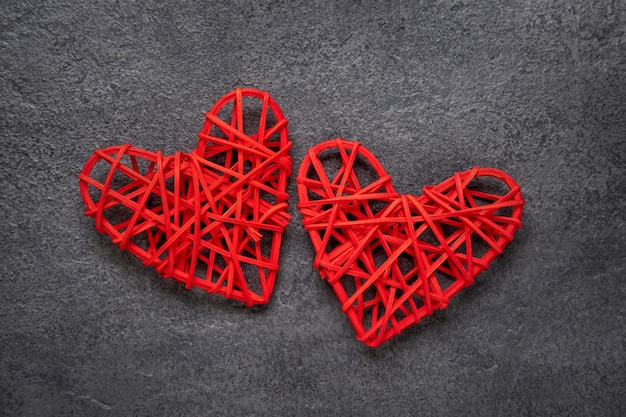 Dois corações vermelhos em um fundo cinza de concreto. conceito de dia dos namorados. vista de cima.