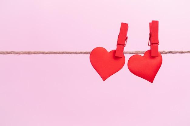 Dois corações vermelhos estão pendurados em clipes com lugar para texto em um fundo rosa