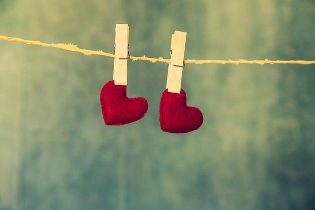 Dois corações vermelhos estão pendurados na corda sobre o fundo azul de madeira.