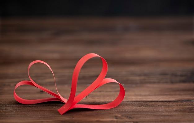 Dois corações vermelhos feitos à mão em fundo de madeira marrom