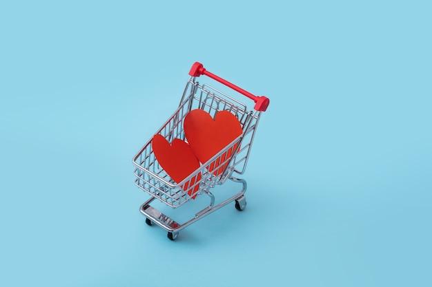 Dois corações vermelhos feitos de papel estavam no carrinho de compras pequeno sobre fundo azul. fechar-se. conceito de dia dos namorados, feliz e amor
