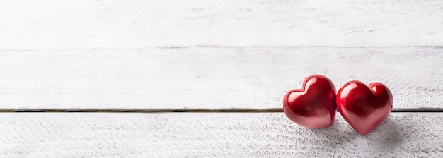 Dois corações vermelhos na mesa de madeira. banner panorâmico romântico para manobristas ou dia do casamento.