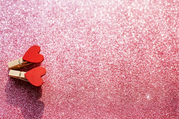 Dois corações vermelhos no fundo desfocado glitter rosa. conceito de dia dos namorados. foco seletivo. copie o espaço.