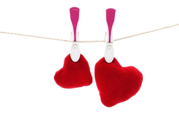Dois corações vermelhos pendurados na corda com prendedores de roupa, isolados no branco.