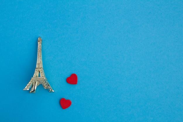 Dois corações vermelhos pequenos e lembrança da torre eiffel na superfície azul.