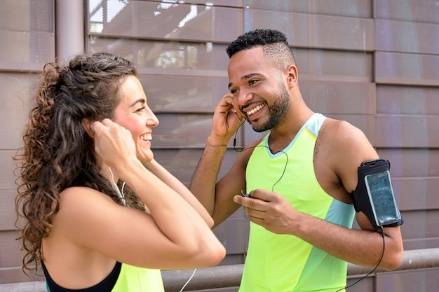 Dois corredores sorrindo alegremente colocando os fones de ouvido nos ouvidos, conectando-os aos smartphones
