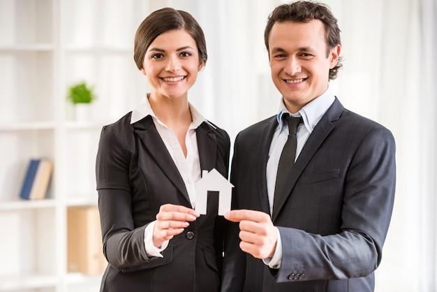 Dois corretores de imóveis em ternos estão mostrando um modelo de casa.