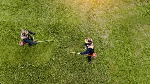 Dois cortadores de grama cortam grama de uma vista superior do zangão