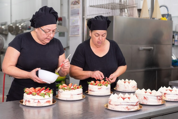 Dois cozinheiros chefe de pastelaria da mulher que trabalham junto fazendo bolos na loja de pastelaria.