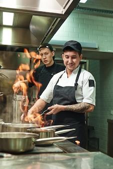 Dois cozinheiros jovens e positivos aprendendo a fazer flambe em comida na cozinha do restaurante