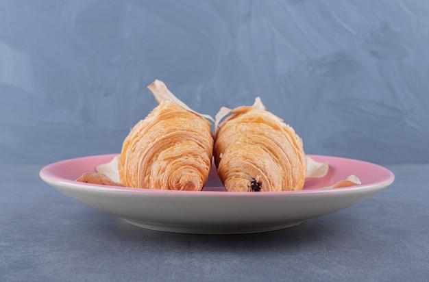 Dois croissant francês fresco no prato sobre fundo cinza.