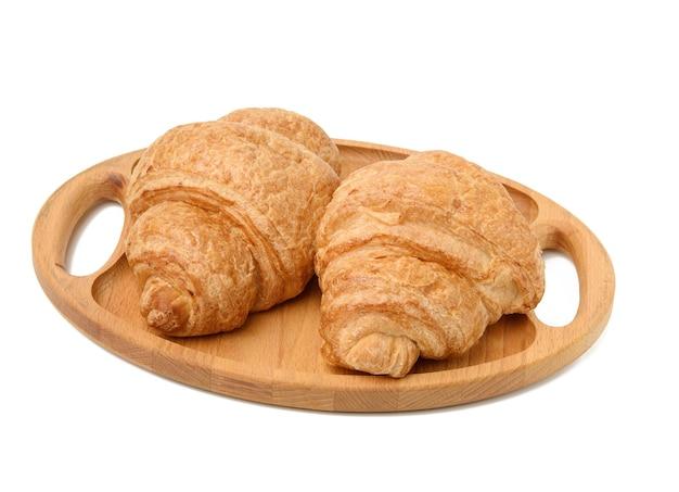 Dois croissants assados repousam em uma bandeja de madeira, comida isolada no fundo branco, close-up