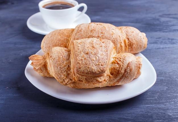Dois croissants com uma xícara de café na chapa branca em fundo preto de madeira
