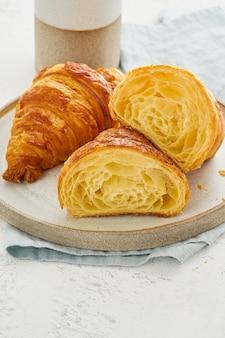 Dois croissants deliciosos no prato e bebida quente na caneca. vista em corte do croissant, mostrando camadas