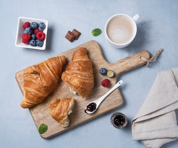 Dois croissants frescos em uma placa de corte e um guardanapo cinza com xícara de café, geléia, mirtilos e framboesas em um fundo cinza.