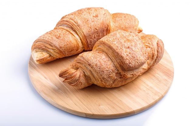 Dois croissants na placa de cozinha de madeira isolada no branco