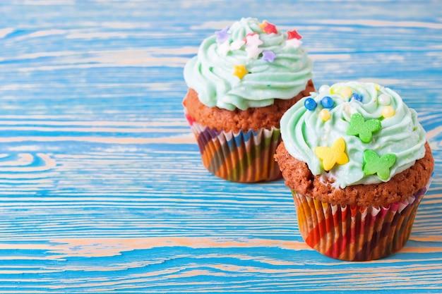 Dois cupcakes artesanais coloridos com creme verde sobre fundo azul de madeira.