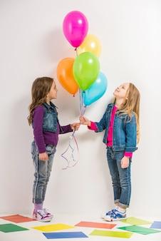 Dois, cute, garotinhas, com, balões coloridos