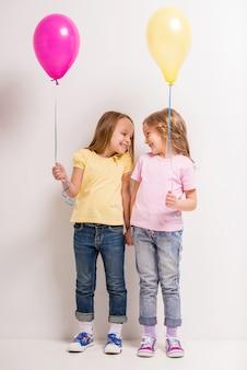 Dois, cute, garotinhas, segurando, balões