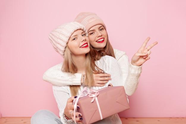 Dois, cute, mulher, com, lábios vermelhos, e, chapéus, dar, presentes, para, um, feriado, e, fazer, paz