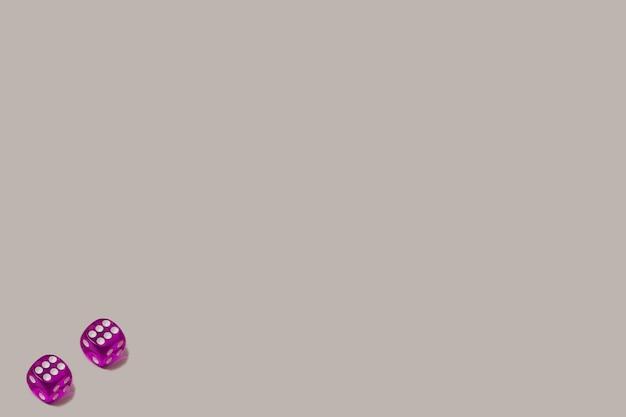 Dois dados de jogo roxos sobre um fundo cinza pastel. chance de sorte e cenário de jogo de azar. espaço negativo e cópia.