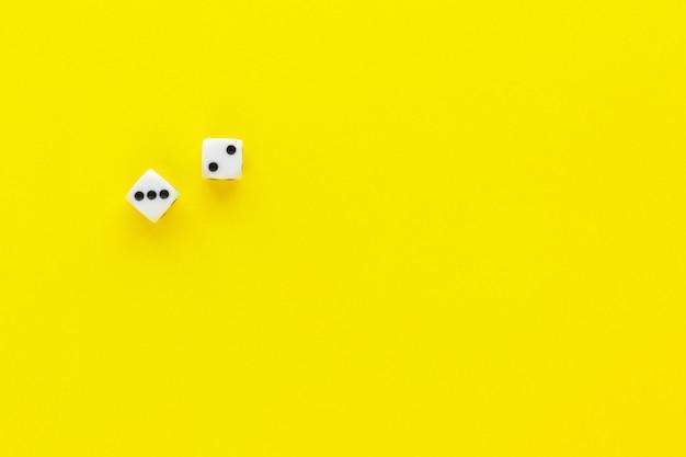 Dois dados mostrando lados diferentes em fundo amarelo. jogando cubo com números. itens para jogos de tabuleiro. camada plana, vista superior com espaço de cópia.