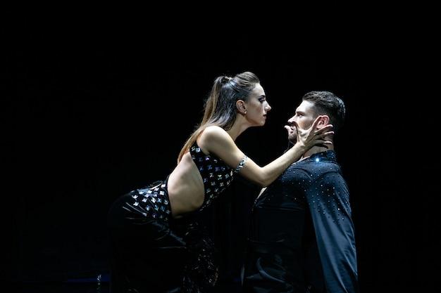Dois dançarinos atuando em preto isolado. homem bonito musculoso e mulher loira atraente