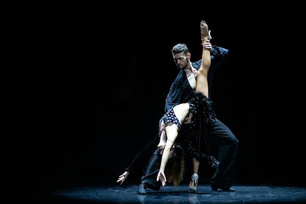 Dois dançarinos atuando em preto isolado. homem musculoso bonito e mulher atraente