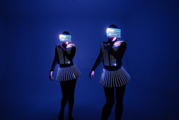 Dois dançarinos de discoteca se movem em trajes de uv.