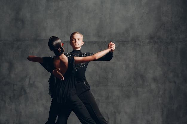Dois dançarinos de tango em traje preto dançando no salão de baile.