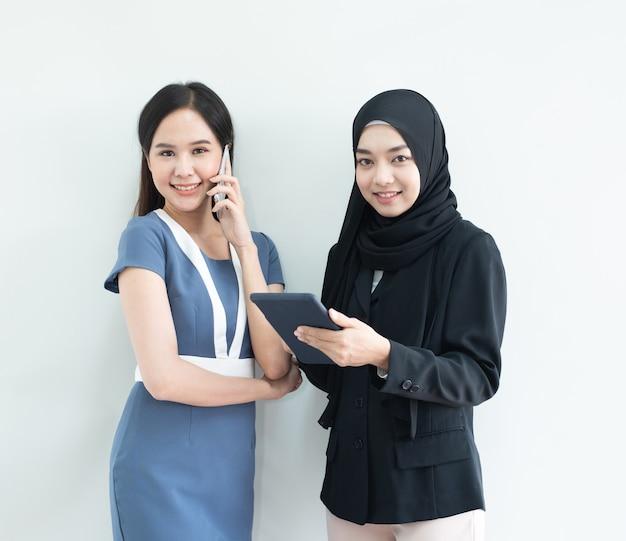 Dois de mulher muçulmana asiática segurar tablet e jovem mulher de negócios asiáticos vestido em um terno moderno com telefone inteligente, conceito de negócio de cooperação de raça mista.