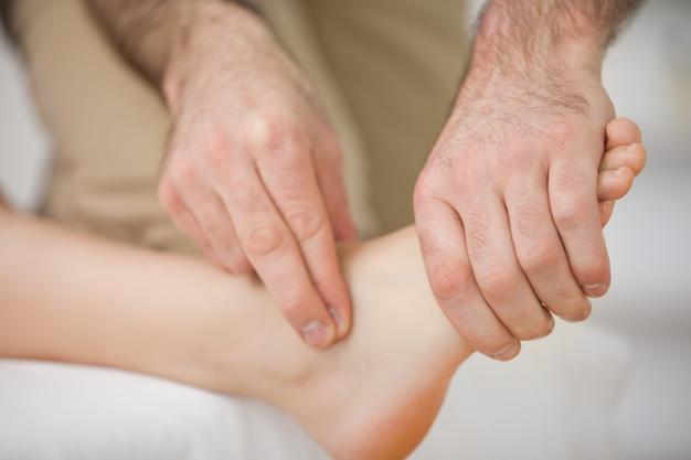 Dois dedos tocando e massageando um pé