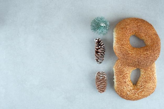 Dois deliciosos bagels com pequena árvore de natal e pinhas.