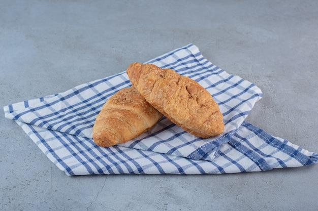 Dois deliciosos croissants doces com toalha de mesa na pedra.