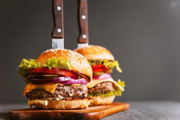Dois deliciosos hambúrguer caseiro de dar água na boca, usado para picar carne. na mesa de madeira os hambúrgueres são facas inseridas.