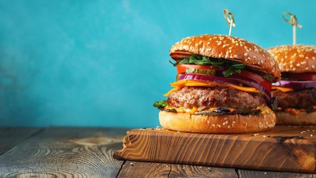 Dois deliciosos hambúrgueres caseiros de carne, queijo e legumes em uma velha mesa de madeira. close de alimentos gordurosos e pouco saudáveis.