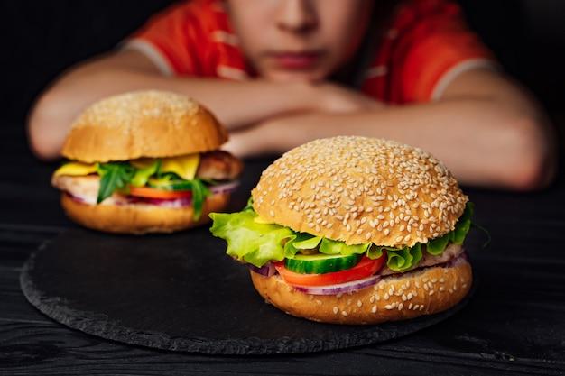 Dois deliciosos hambúrgueres com tomate, carne, pepino verde e alface
